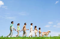 青空のもと一列で歩く家族