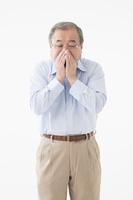 くしゃみをするシニアの日本人男性