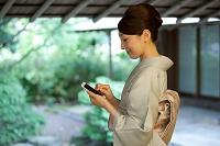 スマートフォンを操作する着物の日本人女性