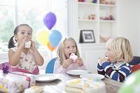 誕生日パーティーでケーキを食べる子供たち