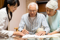 ビジネスウーマンの説明を聞く日本人シニア夫婦