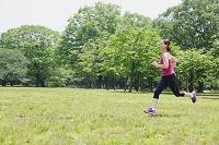 新緑の中でジョギングする日本人女性
