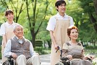 車いすを押す介護士と車いすに座る老人