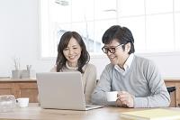自宅でパソコンをみるシニア世代の夫婦