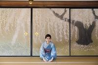襖絵の前で正座する着物の日本人女性