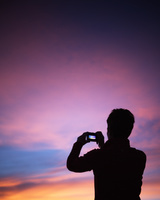 朝焼けの空を撮影するシルエット