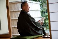 縁側に座って本を読む中高年日本人男性
