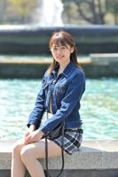 日比谷公園の池のふちに腰かけて微笑む日本人女性