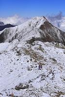 山梨県 間ノ岳から望む縦走する登山者と冠雪した北岳